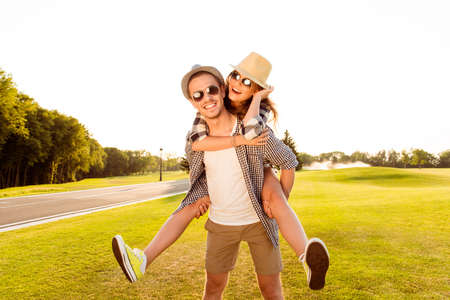 sol radiante: Hombre joven feliz que lleva a cuestas a su novia.