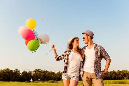 jovem: casal apaixonado caminhando com balões Imagens