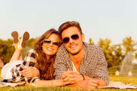 lovers embracing: lovers lying on the grass with glasses Stock Photo