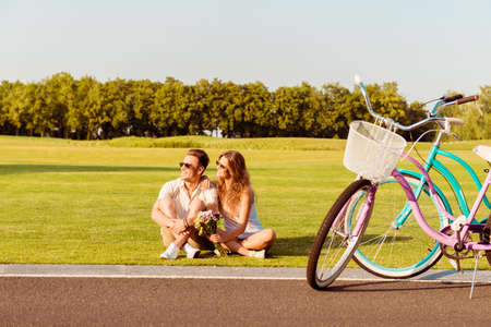 young couple sitting on the lawn near their bicycles 스톡 콘텐츠