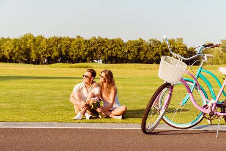 jong koppel zittend op het gazon in de buurt van hun fietsen Stockfoto