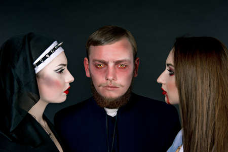 succubus: Halloween. A man and women dressed as the clergy