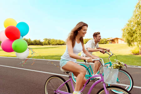 bicycle walk: couple in love  riding a bicycle race with balloons