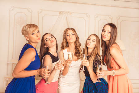 hen party: Bride with bridesmaids pouting lips with glasses Stock Photo