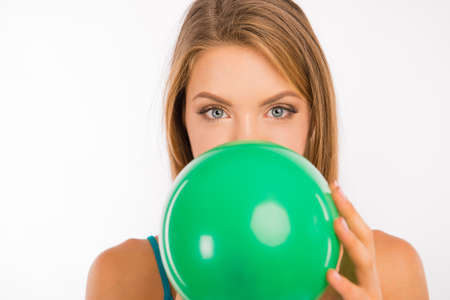 inflating: Attractive girl with green eyes inflating a balloon