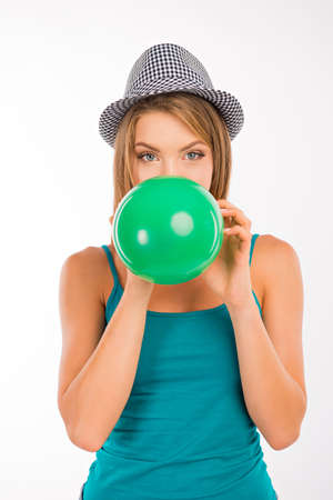 inflating: Attractive girl inflating a green balloon Stock Photo