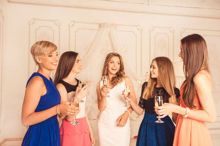 girls celebrate a bachelorette party of bride with champagne