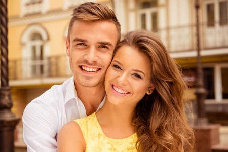 parejas caminando: Hermosa joven pareja en el amor que abraza y sonriente