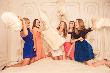 meisjes vieren een vrijgezellenfeest van de bruid. bruidsmeisjes vechten hoofdkussens