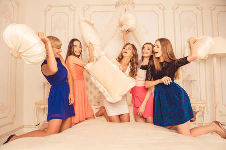 girls celebrate a bachelorette party of bride. bridesmaids fighting pillows