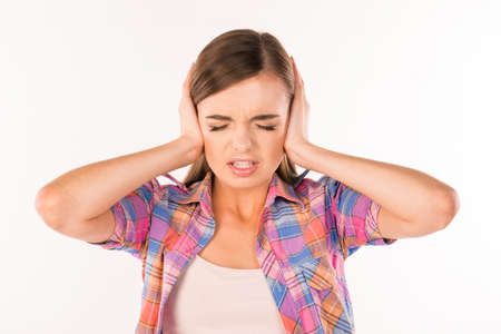hands covering ears: This is too loud! Girl with her hands covering ears Stock Photo