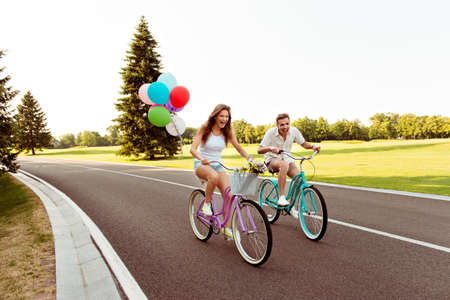 love story: positive happy couple in love ride bicycles have fun