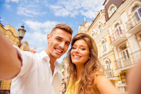 street love: couple making selfie photo on a background of the city