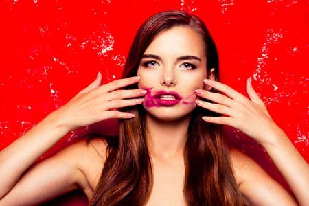 pomatum: beautiful model on a red background rubbing lipstick