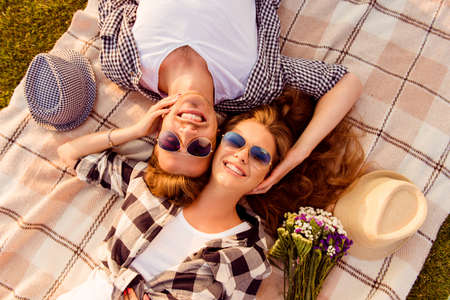 top view of a couple in love lying on a picnic plaid