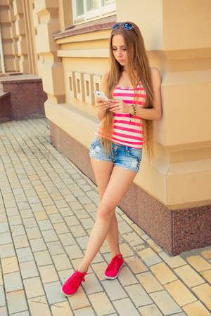 leggy girl: leggy girl looks in her phone on the street