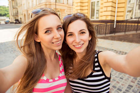 making faces: Friends making selfie. Two beautiful young women making selfie photo Stock Photo
