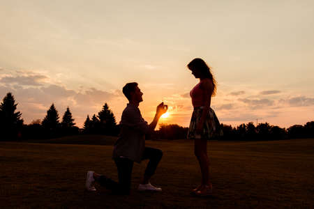 betrothal: silhouette of a man makes a proposal of betrothal to his girlfriend Stock Photo