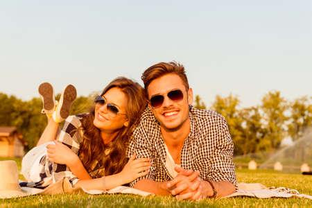 personas felices: amantes tumbado en la hierba con gafas