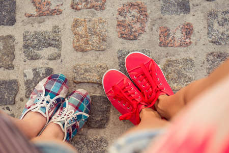 blue top: top view of a two pairs of sneakers shoes walking on paving ston