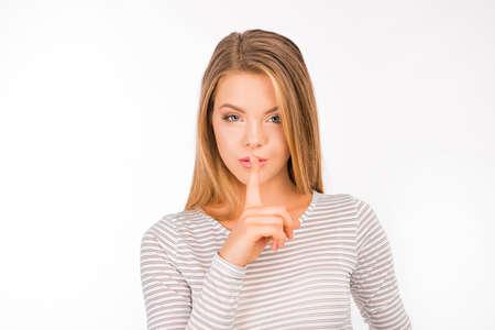 Serious girl in shirt holding finger on lips Stock Photo
