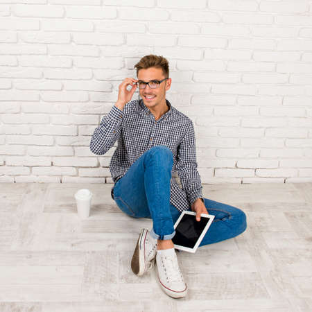 young male model: man sitting on the floor with digital tablet Stock Photo
