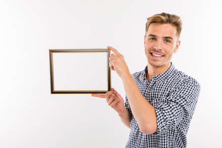 Handsome man holding a picture frame