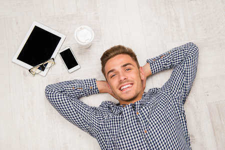 men shirt: Top view of man lying on the floor with tablet, coffee and phone