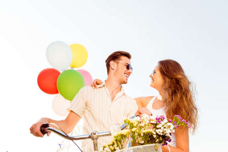 parejas de amor: pareja de enamorados en bicicletas con globos y flores Foto de archivo