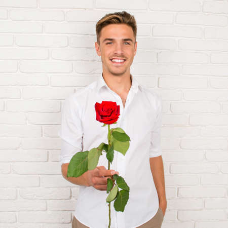 hombre romantico: Romantic man gives a red rose
