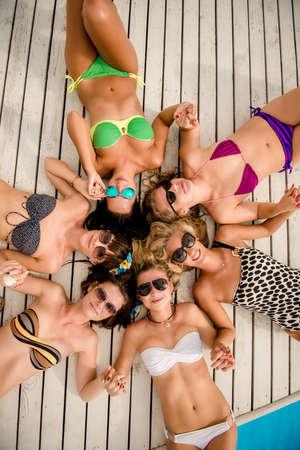 despedida de soltera: ni�as felices en la playa. hermosas amigas se encuentran en el suelo blanco de madera cerca de la piscina. ni�as acostado en la espalda