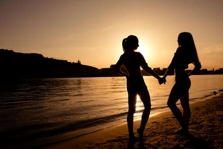 black couple: silhouettes of girlfriends at sunset Stock Photo
