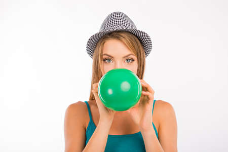 inflating: Cute girl inflating green balloon Stock Photo