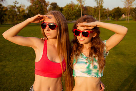 sex discrimination: Two young slender girls watching sunset in the park Stock Photo