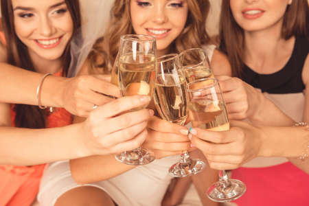 clink: Girls during a holiday smile and clink glasses