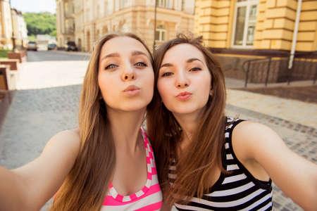 haciendo el amor: Dos hermosas mujeres jóvenes haciendo selfie foto