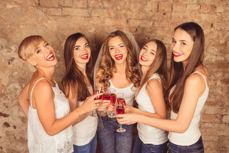 hens: Beautiful bride with happy bridesmaids celebrating hen-party with red champagne