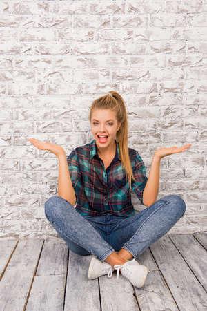 winning mood: cheerful gesturing girl sitting on the floor
