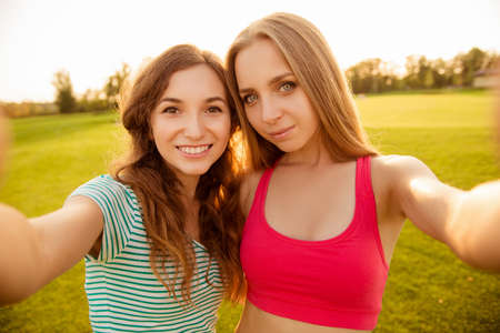 two nice-looking cheerful girls making selfie photo