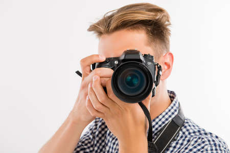 handsome young photographer taking a photo of a viewer