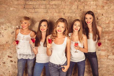 dress code: Joyful young women wearing dress code celebrating with sparkling wine