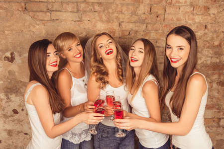 up code: Attractive bride and happy bridesmaids celebrating hen-party with red champagne