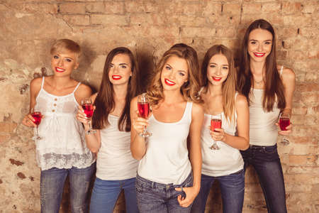 dress code: Beautiful young women wearing dress code celebrating with red champagne