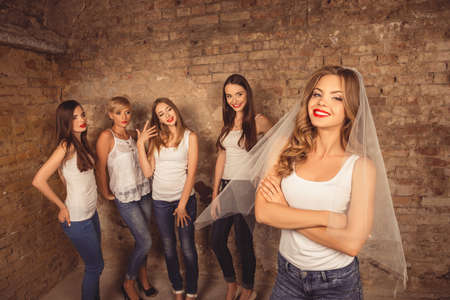hen party: Beautiful bride standing in front of her bridesmaids celebrating hen-party