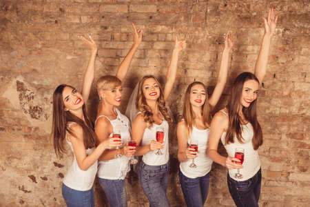 red hen: joyful bride and happy bridesmaids celebrating hen-party with red champagne