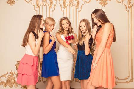 bridesmaids: Happy bride showing her surprised bridesmaids wedding ring Stock Photo