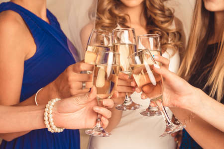 clink: at party happy girls clink their glasses with champagne