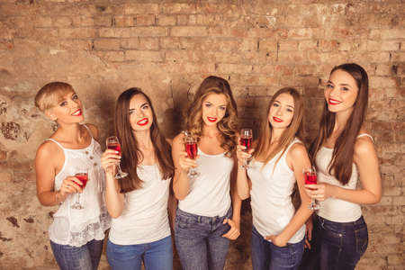 dress code: Cheerful young women wearing dress code with sparkling wine