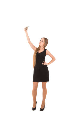 short dress: girl in a black short dress on a white background. girl photographing Selfe Stock Photo