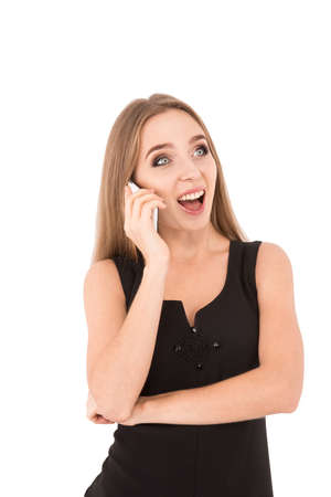 phon: girl in a black dress on a white background. girl talking on the phon Stock Photo